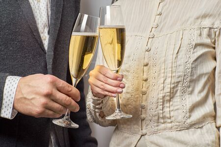 Male and female hands hold glasses of champagne Фото со стока