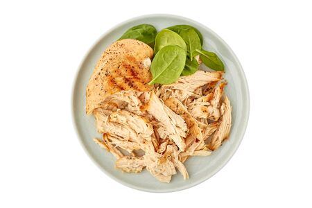 Plate with pulled chicken breast on white Фото со стока