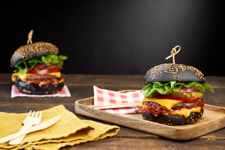 Two juicy black hamburgers on dark wooden background. Fast food concept, copy space