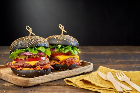 Two black hamburgers on dark wooden background. Fast food concept, copy space