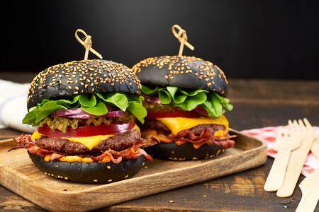Two huge black hamburgers on dark wooden background. Fast food concept Фото со стока
