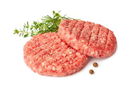 Two raw burger patties with thyme and reosemary on white