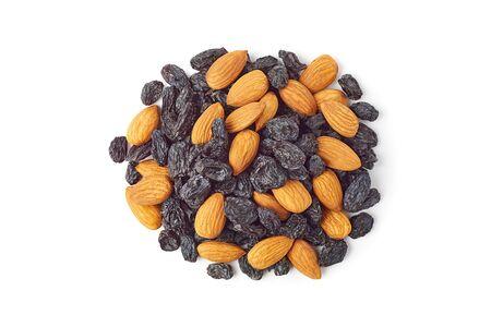 Heap of almonds and black raisins on white