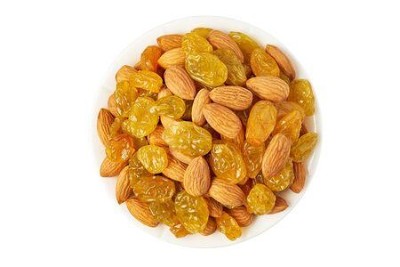 Bowl of almonds and sultana raisins on white Фото со стока