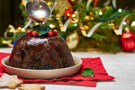 Burning christmas pudding on decorated fir tree background