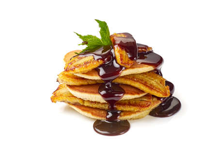 Stack of pancakes with fried banana, mint leaf and chocolate syrup on white Фото со стока