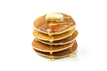 Stack of pancakes with butter and honey on white
