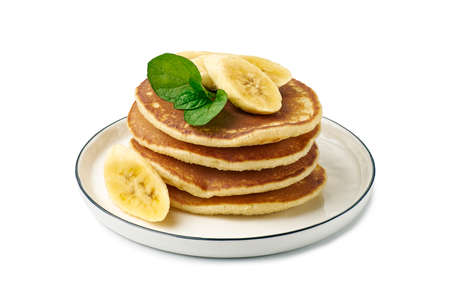 Stack of pancakes with banana and mint leaf on dish over white Фото со стока