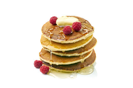 Stack of pancakes with butter, honey and raspberries on white Фото со стока