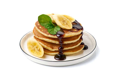 Stack of pancakes with banana,mint leaf and chocolate syrup on white