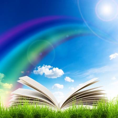 Open book in green grass over blue sky. Magic book Stock Photo