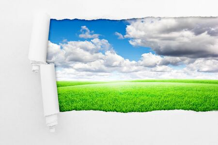 shred: Closeup of a hole in paper over nature background. Field with blue clouds sky Stock Photo