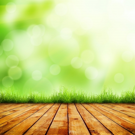 Fresh spring green grass with green bokeh and sunlight and wood floor. Beauty natural background photo