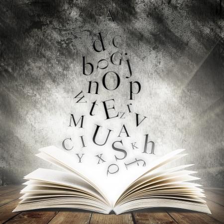 libros volando: Viejo libro abierto con la luz mágica y letras que caen sobre tarimas de madera y fondo abstracto oscuro Foto de archivo
