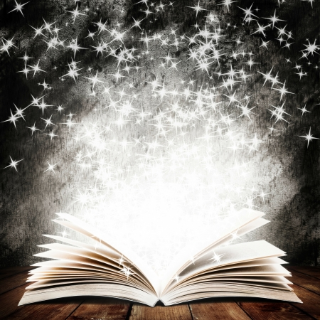 open spaces: Old open book with magic light and falling stars on wood planks and dark abstract background