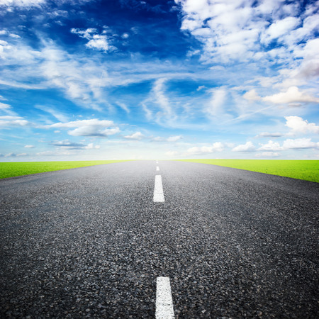 asphalted highway over blue sky with white clouds background photo