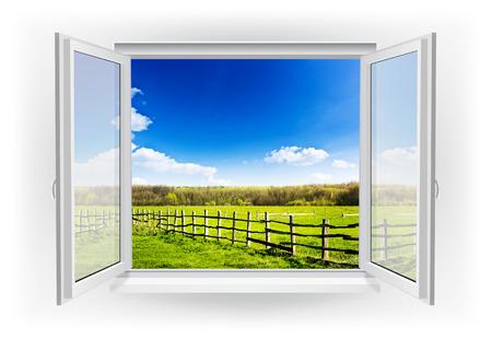 ventana abierta: Abra la ventana con el campo verde con la cerca bajo el cielo azul sobre un fondo Foto de archivo