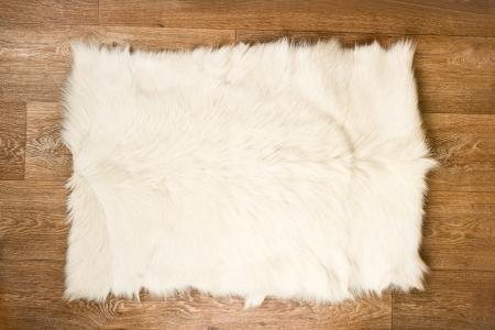 sheep skin: Decorative fur carpet on wood floor