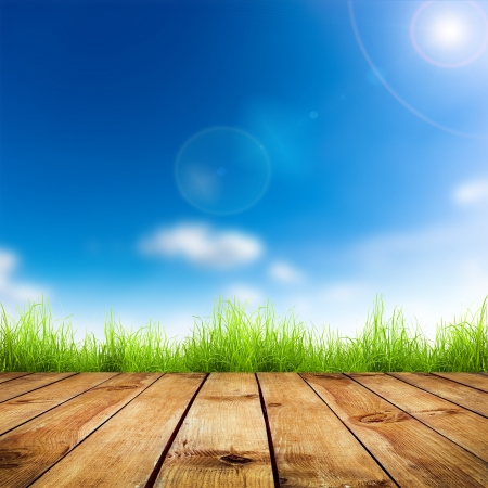 blue sky and fields: Fresh spring green grass with blue bokeh and sunlight and wood floor.