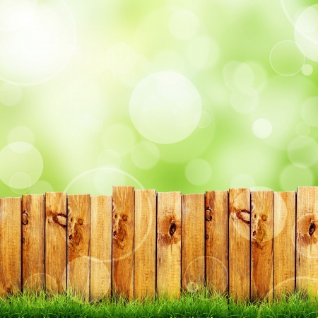 Wooden fence and green grass against green bokeh sky background