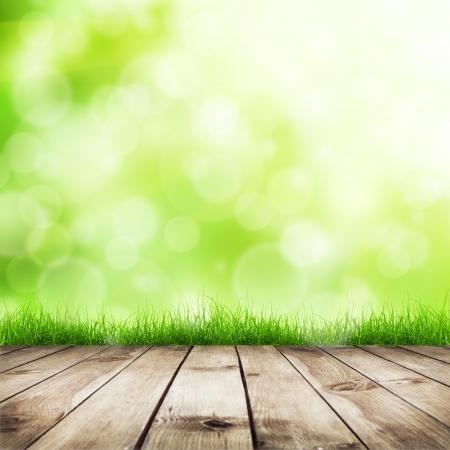 グリーンのボケ味と日光と木の床の自然な背景と新鮮な春の緑の草