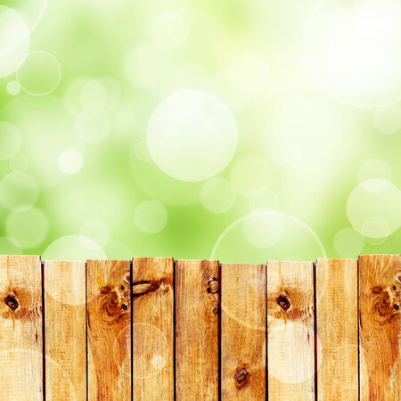 knothole: Wooden fence against green bokeh sky background
