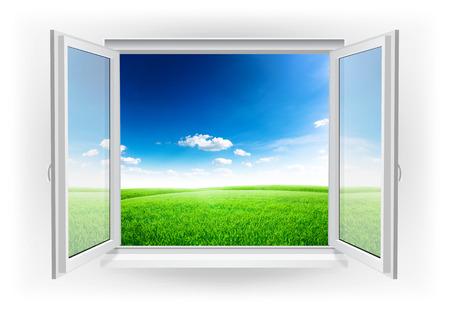Offene Fenster mit grünen Wiese unter blauem Himmel