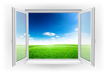 Open window with green field under blue sky
