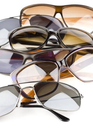 Assorted styles of tinted sunglasses on white background photo