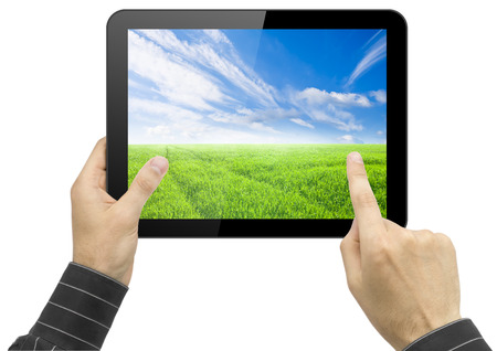 Black tablet pc with nature wallpaper in hands on white background. Portable computer photo