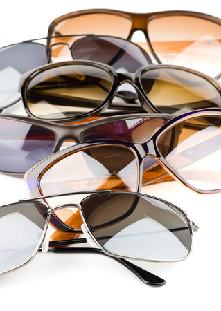 Collection of assorted styles of tinted sunglasses on white background photo