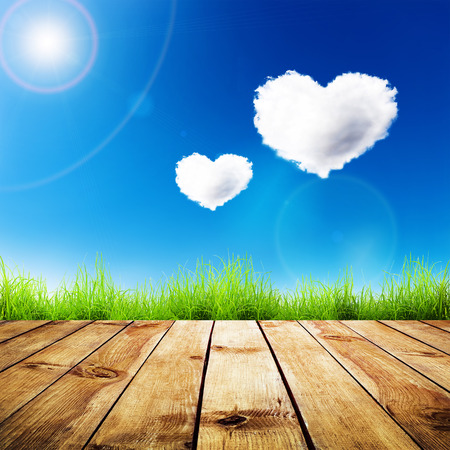 Green grass on wooden plank over a blue sky with hearts shape clouds  Beauty natural background photo