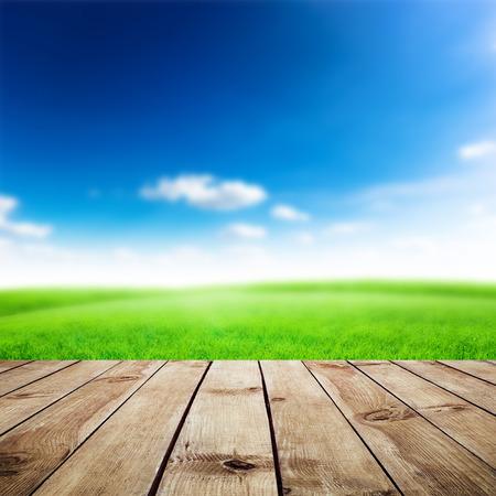 Groen veld onder de blauwe hemel. Houten planken vloer. Beauty natuur achtergrond Stockfoto