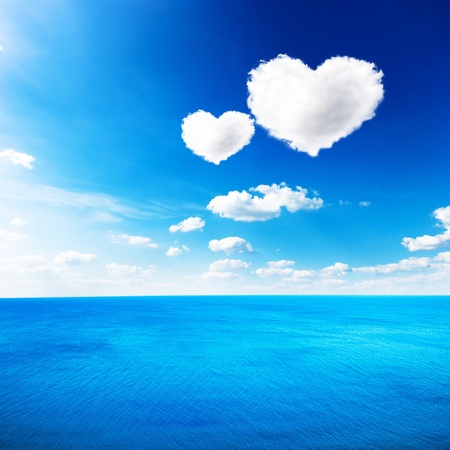 heart under: Blue sea under clouds sky with heart shape cloud background