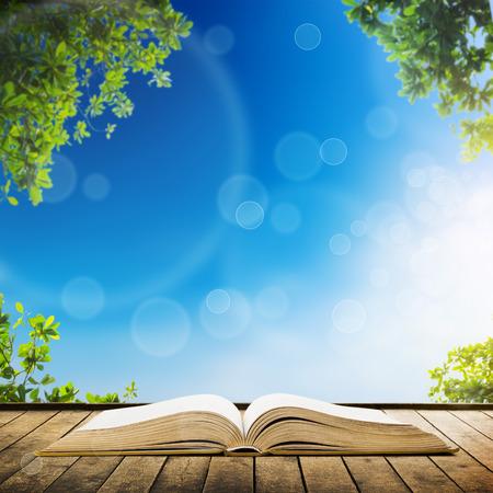 Open boek op houten planken over hemel met bladeren achtergrond