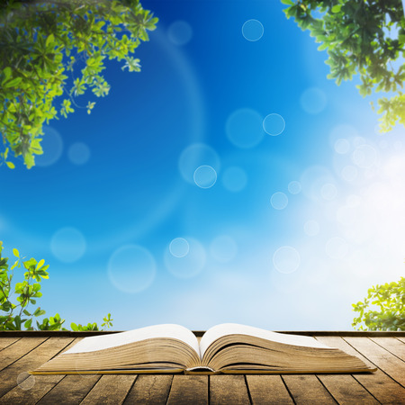Open book on wood planks over sky with leaves background