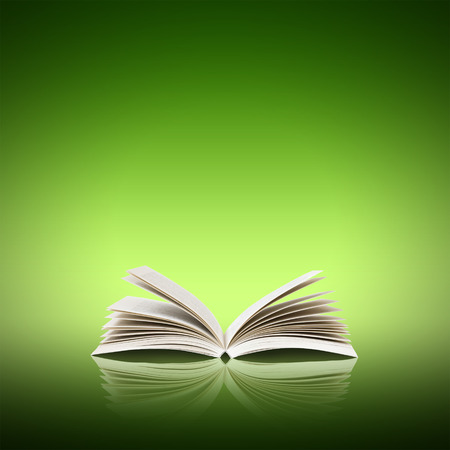 open life: Open book isolated on green background