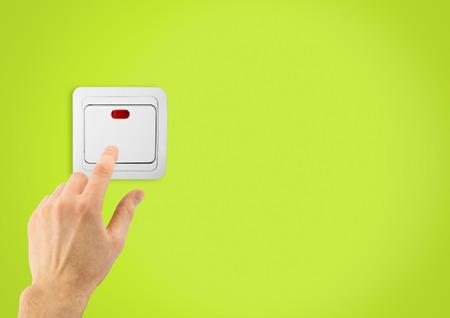 Einfacher Lichtschalter und Hand auf einem grünen Wandhintergrund Standard-Bild - 34031277
