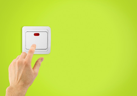 light switch: Simple light switch and hand on a green wall background Stock Photo