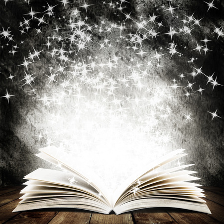 Old open book with magic light and falling stars on wood planks and dark abstract background