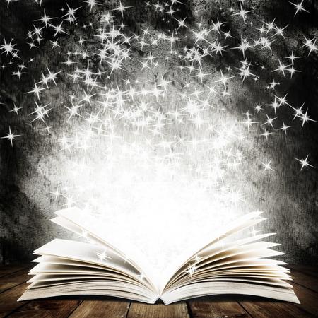 moudrost: Staré otevřená kniha s kouzelným světlem a padající hvězdy na dřevěné podlahy a tmavém pozadí abstraktní Reklamní fotografie