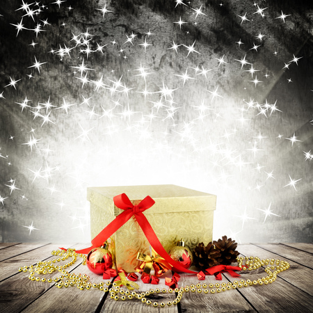 Golden christmas gift box with christmas balls on wood planks over dark background with light rays with stars photo
