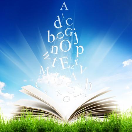 libros volando: Abra el libro con las cartas de vuelo en la hierba verde sobre fondo de cielo azul. Libro mágico
