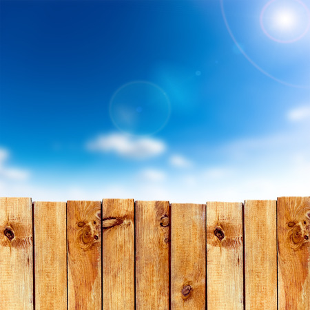 picket fence: Wooden fence against blue sky background