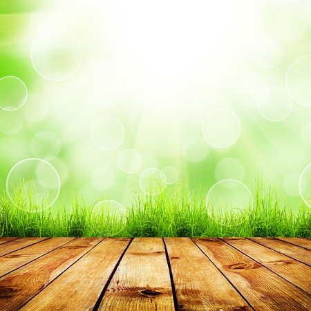 Fresh spring green grass with green bokeh and sunlight and wood floor. Natural background