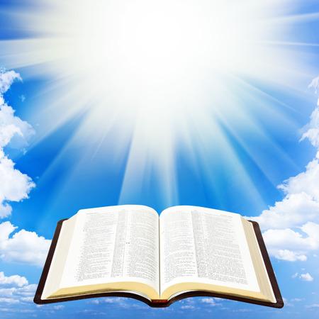 空の背景で開く聖書本