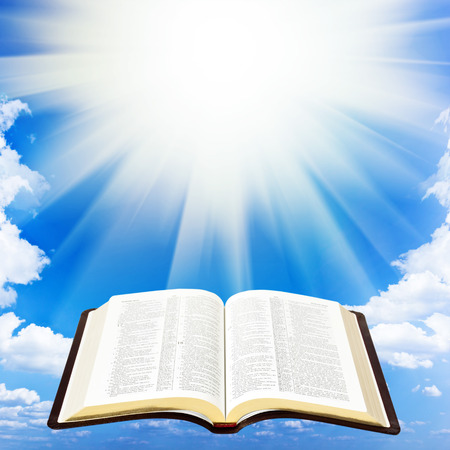 Open bible book over sky background