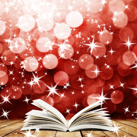 book background: Old open book with magic light and falling stars on wood planks and dark abstract background