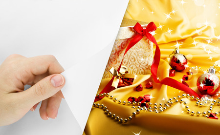 Blank sheet of paper with hand opening it. Golden gift with lights. Christmas background photo