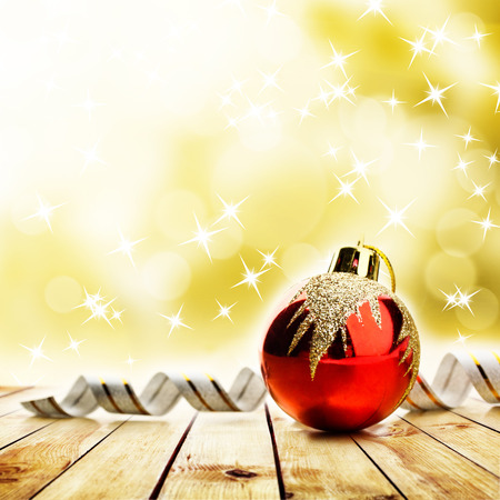 Red christmas toy on wood planks over abstract bright yellow background photo